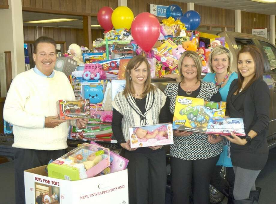 Eddie Ashburn, general manager of Reagor-Dykes Ford-Lincoln-Toyota, and employees Kate Phillips, Millie Duncan, Heather Riley and Stacy Juarez pose with some $3,000 worth of toys being kept in the back of a pickup on the showroom floor. The toys, purchased with money donated by employees at Reagor-Dykes dealerships in Plainview, Lubbock and Lamesa, will be given to needy children through the U.S. Marines' Toys for Tots program. Photo: Jason Johnson/Plainview Herald