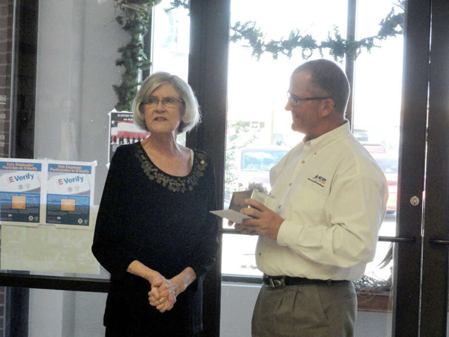 Danny Glenn, president of American State Bank Plainview, presents retiring Assistant Vice President Suzy Quisenberry with a gift from ASB for 19 years of service during a reception held in her honor Tuesday at the bank.