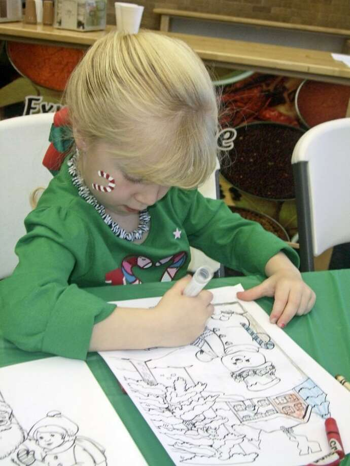 Five-year-old Taylor, daughter of Ashley Ulrey of Plainview, colors a winter scene during Saturday morning's Breakfast with Santa at Wayland's McClung Center. More than 200 gift bags were given to kids who got to enjoy a variety of activities in addition to visiting with Santa and Mrs. Claus. The annual event is sponsored by RSVP. (See related video.)