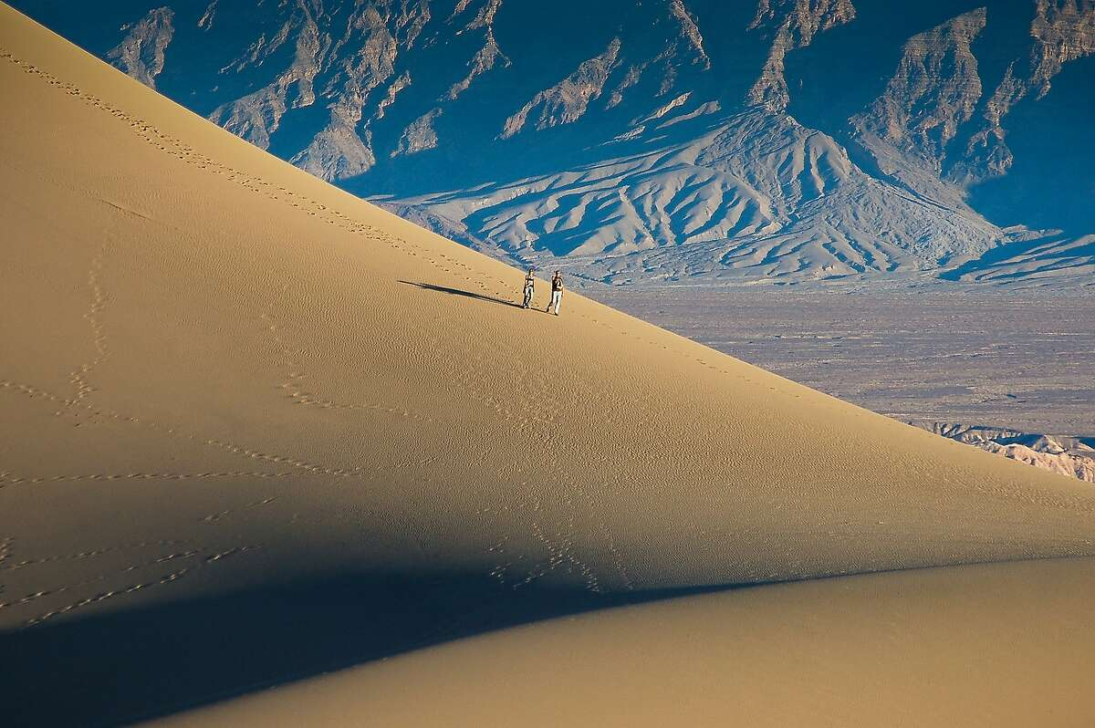 MORE VIEWS OF DEATH VALLEY: Hikers descend an enormous dune at Death Valley National Park's Mesquite Flat Sand Dunes.