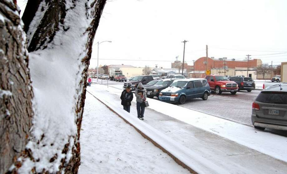 Doug McDonough/Plainview HeraldAmid a frosty backdrop of blowing snow and frigid temperatures, Ash Sixth Grade students brave icy sidewalks and streets as they head to school Monday morning. Plainview and most of the area received about an inch of snow Sunday night and Monday morning with another half-inch falling by mid-afternoon. Total snowfall accumulations of 2-3 inches were expected before the precipitation was to end early today. Bitter cold temperatures should continue today with the mercury rising only into the mid-20s before plunging to about 11 tonight. The high on Wednesday should be in the lower 40s, but the early-morning wind chill readings could drop to zero.