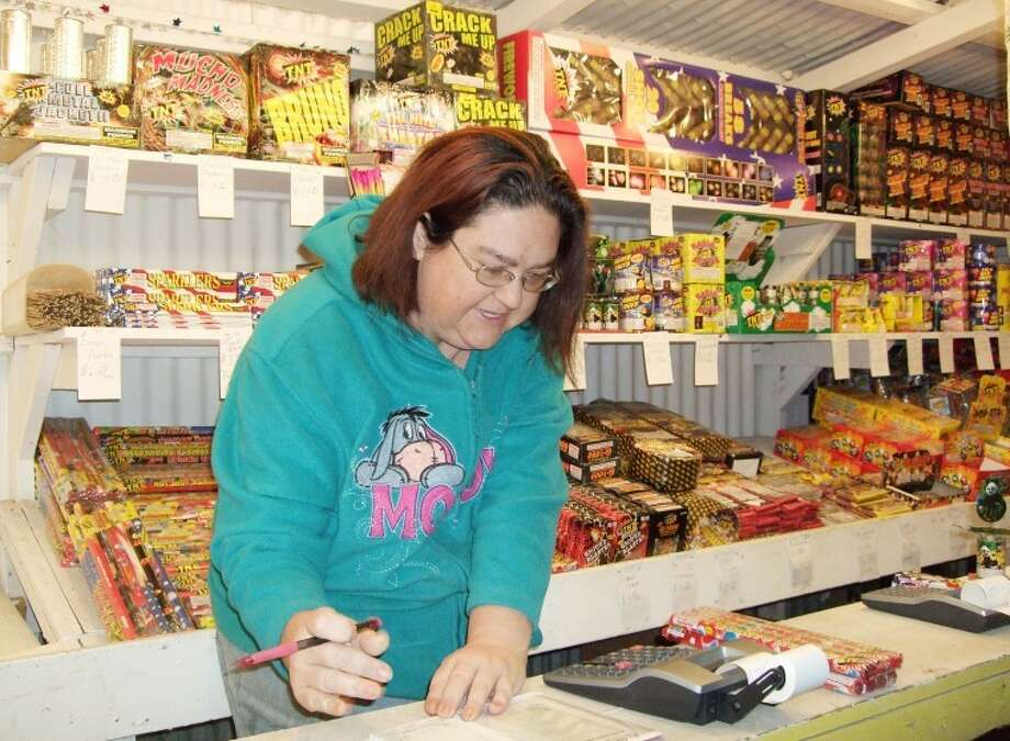 Keisha Haley sells firecrackers at a TNT Fireworks stand owned by her father, Ronald McCartie. The otherwise stay-at-home mom, who sometimes substitute-teaches, has been selling fireworks for the Fourth of July and New Year's Eve celebrations since 2008. Photo: Shanna Sissom/Plainview Herald