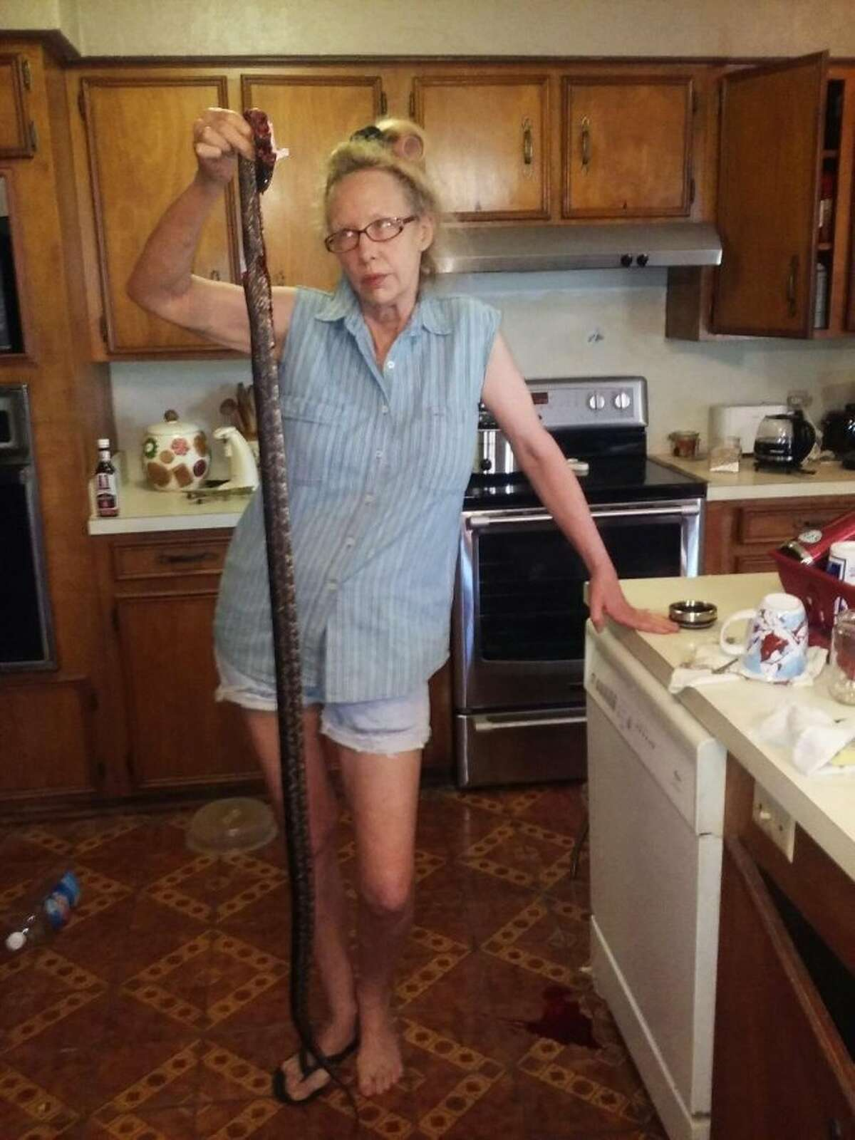Deborah Burdette, from Willbarder County, and one of the snakes she found in her kitchen and killed.