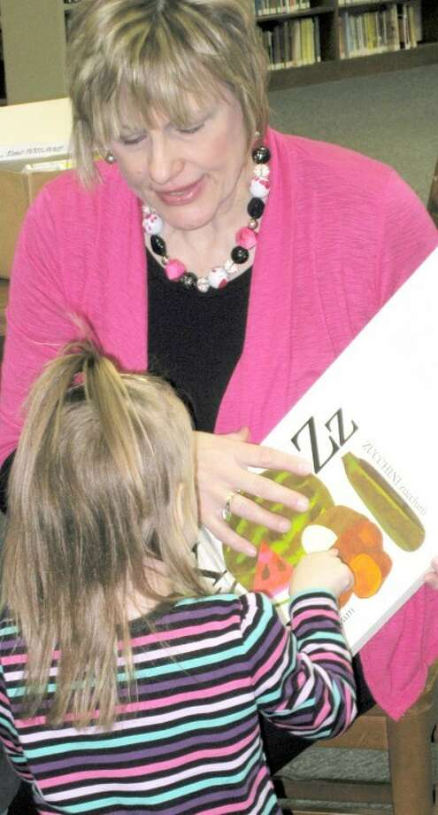 "Preschooler Paige Truett gets help learning the alphabet from Hale County Family & Consumer Sciences Extension agent Deana Sageser as they read Lois Ehlert's ""Eating the Alphabet: Fruits & Vegetables from A to Z"" during Unger Library's pre-school story time. All 3-5 year olds and their parents are invited to the library at 10 a.m. each Wednesday for the reading program."