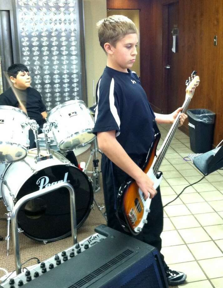 Courtesy Photo by Isabel PenaRyan Vera plays drums and Jayden King the guitar last week at a Christmas open house at Wells Fargo.