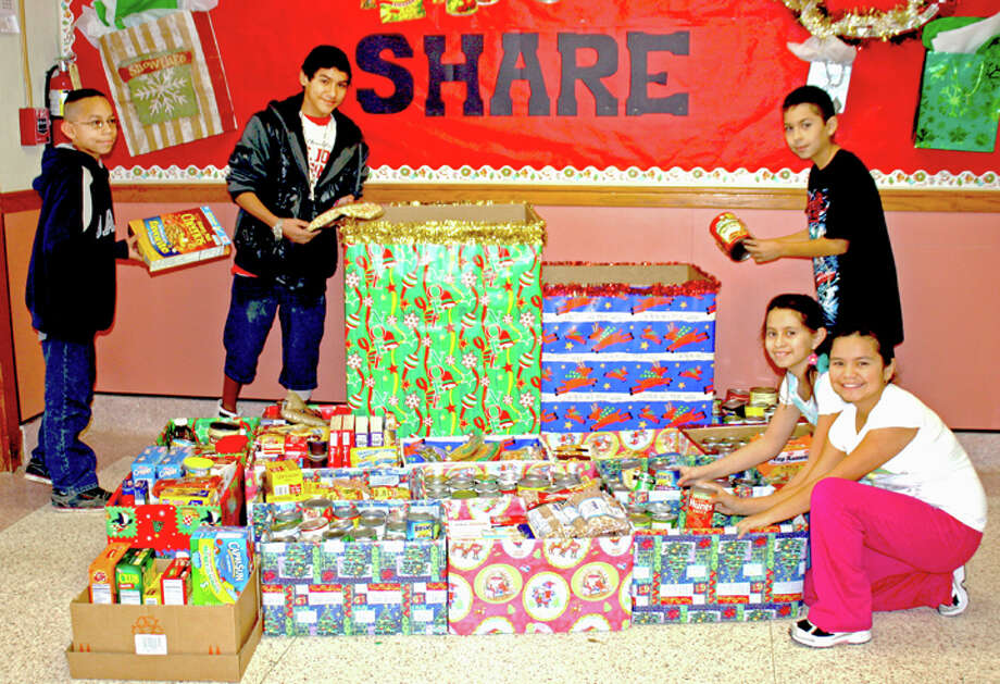 Jan Seago/Plainview ISDAsh Sixth Grade Learning Center Book Club members Isaiah Riojas (left), Ranson Fuentes, Fernando Carrillo, Kimberly Cervera and Milly Meza pack food they collected and plan to donate to Faith in Sharing House (FISH). The club has collected more than 500 pounds of food so far and is working toward a goal of 1,000 pounds in the coming week.