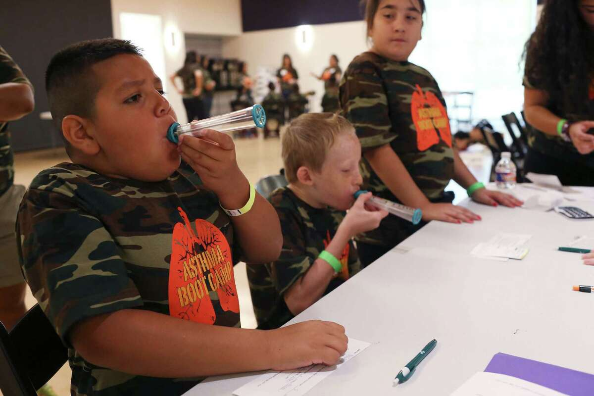 Joshua Leos, 9, (left) and Zeke Castillo, 9, use peak flow meters as Mirakle Garcia, 12, watches during UTHSC's free asthma boot camp for children at the DoSeum. Children ages 7-12 spent the day Monday learning how to manage the disease.