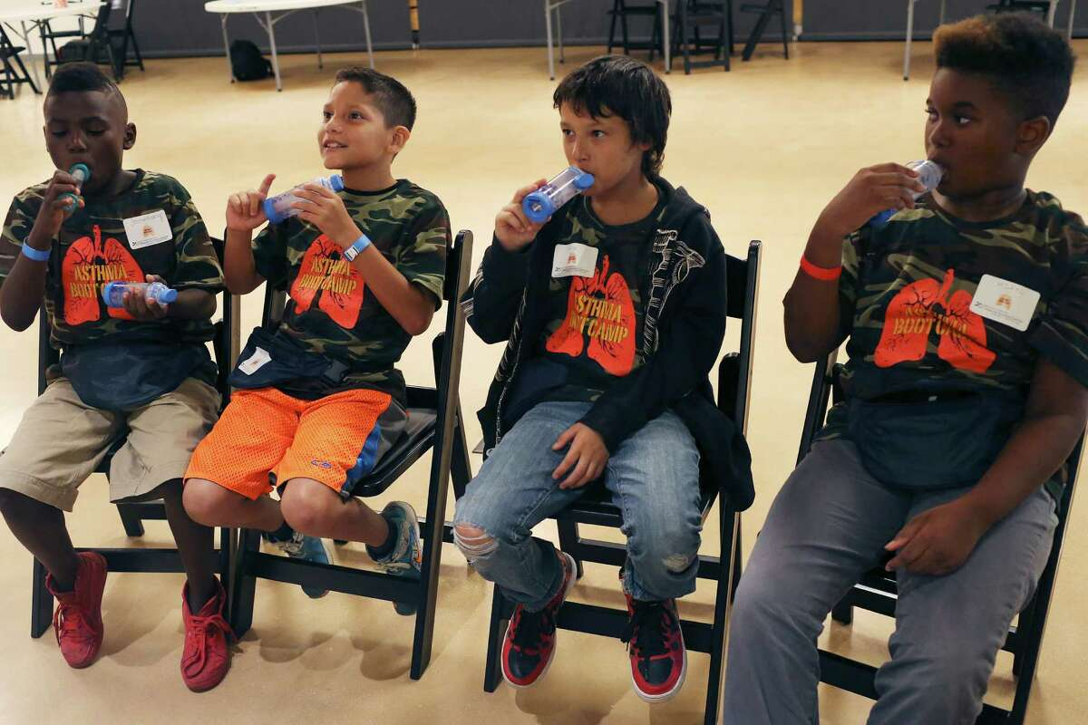 From left, Joe Anthony Holmes, 9, Armando Hernandez, 9, Gage Acevedo, 11, and Mikyl Vance, 10, try spacer devices during a free asthma boot camp hosted by the University of Texas Health Science Center San Antonio at the DoSeum, San Antonio?'s Museum for Kids, Monday, July 25, 2016. The camp is for children ages 7-12 and will help them learn about asthma prevention and triggers, among other critical information. Officials say asthma is a leading cause of absenteeism from school. The spacer devices are to facilitate the use of metered-dose asthma inhalers.