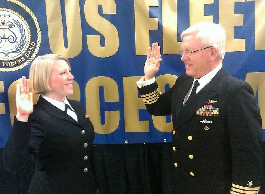 Courtesy PhotoDr. Charles Starnes, associate professor of economics and finance at Wayland and a retired U. S. Navy captain, re-enlists his daughter, Emily Charleton, in Norfolk, Va., where she is a vocalist with the U.S. Fleet Forces Band. The ceremony was held at the band's headquarters on Friday.