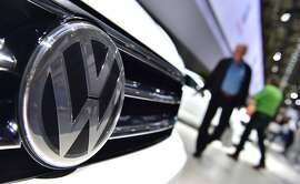 """(FILES) This file photo taken on June 22, 2016 shows a Volkswagen logo on a VW Tiguan on display during German carmaker Volkswagen shareholders' annual general meeting in Hanover.  A federal judge in California granted preliminary approval on July 26, 2016 to a $14.7 billion settlement over Volkswagen's emissions cheating scandal.""""There's been an enormous effort to achieve a series of goals,"""" said San Francisco district judge Charles Breyer. """"I think these goals have been achieved,"""" he said, setting an 18 October deadline for final approval of the deal.  / AFP PHOTO / JOHN MACDOUGALLJOHN MACDOUGALL/AFP/Getty Images"""