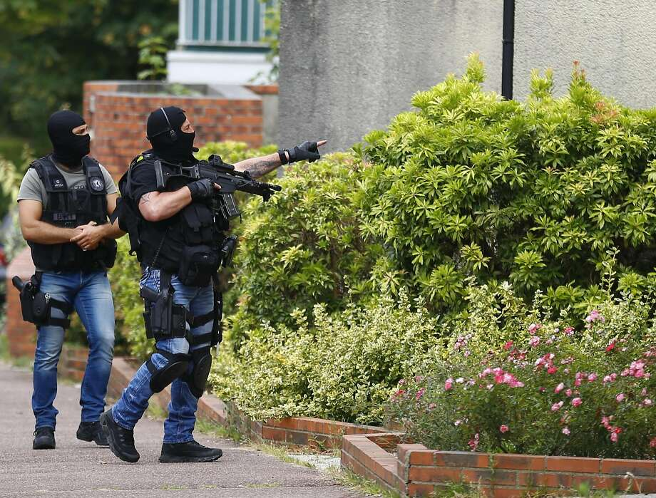 Hooded Police officers conduct a search in Saint-Etienne-du-Rouvray, Normandy, following an attack on a church that left an 85-year-old priest dead. Photo: Francois Mori, Associated Press