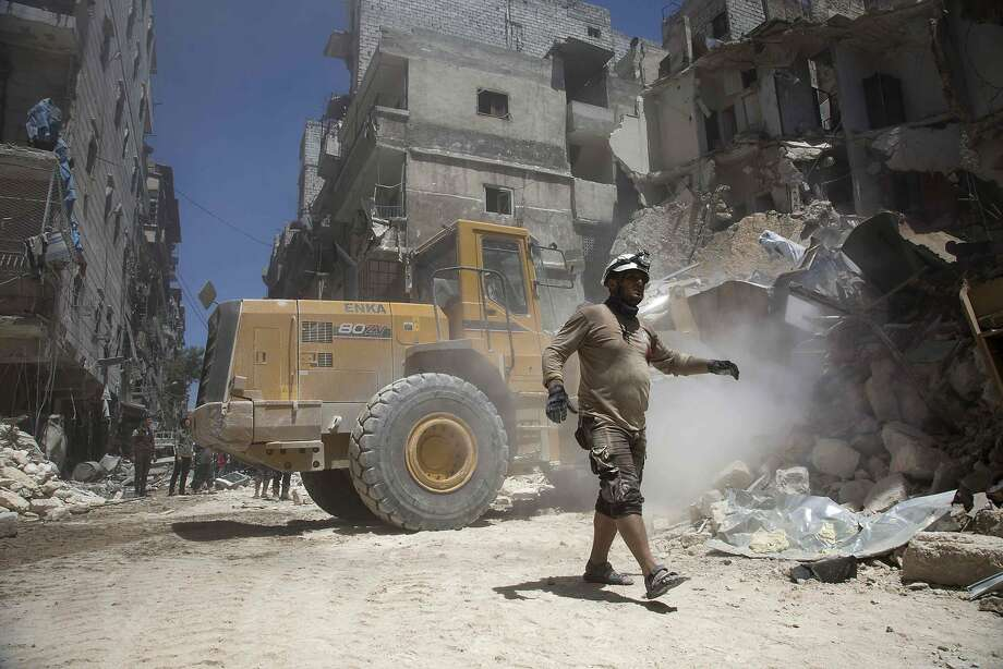A rescue worker in Aleppo, Syria, walks away from a bulldozer clearing rubble following air strikes. Photo: KARAM AL-MASRI, AFP/Getty Images