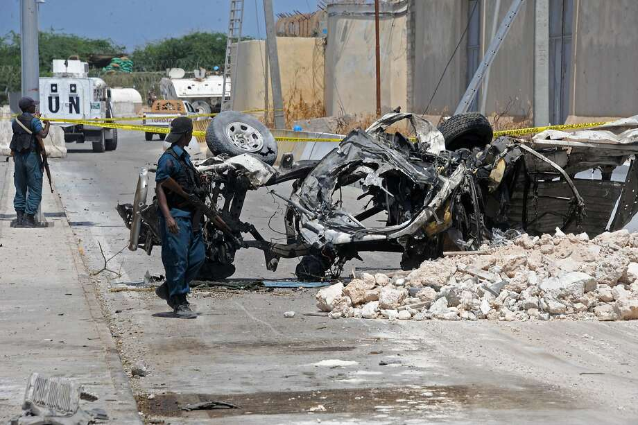 TOPSHOT - Somali soldiers pass near the wreckage of a car bomb outside the UN's office in Mogadishu on July 26, 2016.   At least 13 people were killed on July 26 in twin bombings near UN and African Union buildings adjoining Mogadishu's airport, police said, in what the jihadist Shabaab group claimed as a suicide attack. / AFP PHOTO / MOHAMED ABDIWAHABMOHAMED ABDIWAHAB/AFP/Getty Images Photo: MOHAMED ABDIWAHAB, AFP/Getty Images