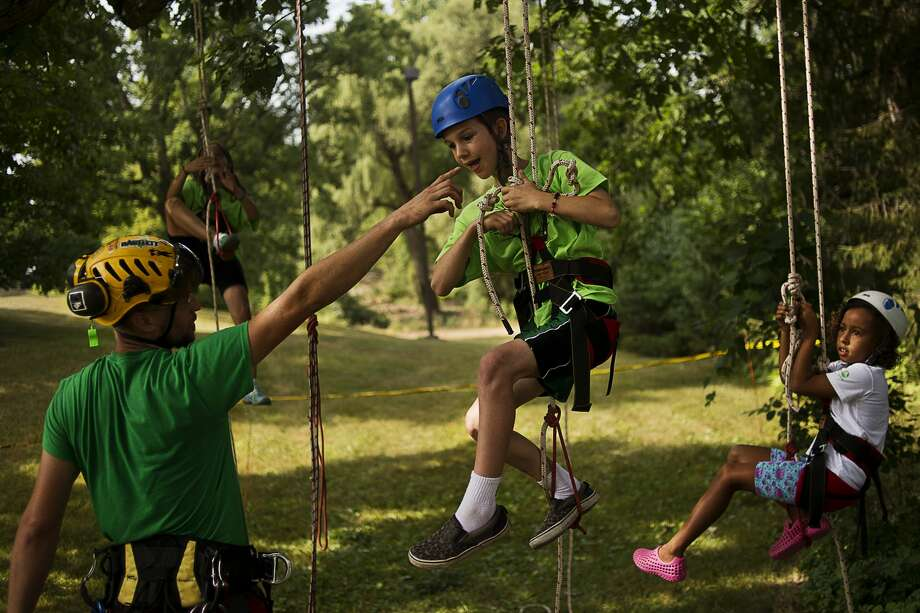 From left, Dow Gardens tree specialist Brian Siler shows Midland resident Caleb Ellis-Hitchins, 9, the ropes as Essexville resident Pearl Norton, 8, looks on during Recreational Tree Climbing for Kids on Thursday at Dow Gardens Whiting Forest. This is the second year that Dow Gardens has partnered with Advanced Arborist to provide tree climbing classes. This year they have doubled the amount of classes with the next session on Aug. 16th. The Michigan Tree Climbing Championships will be held on Sept. 17th at Revere Park. Photo: Erin Kirkland/Midland Daily News/Erin Kirklamd