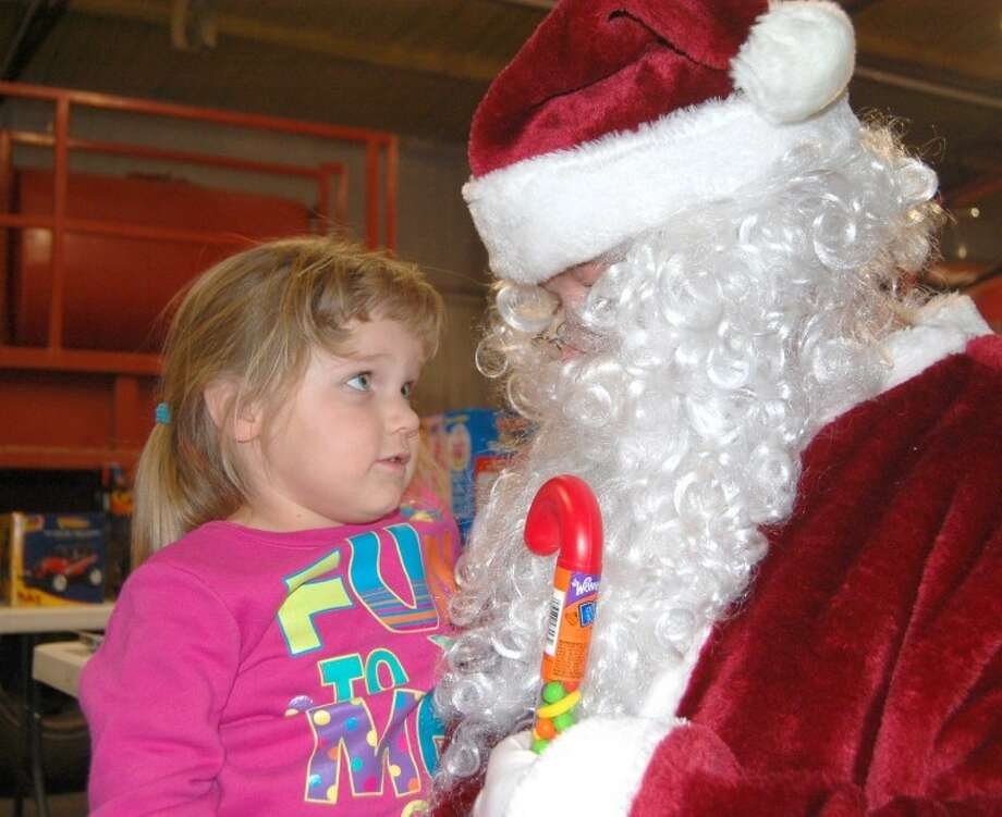 Doug McDonough/Plainview HeraldThree-year-old Kendrie Milstead makes sure Santa understands what she wants for Christmas. She stopped off at the Hale Center Volunteer Fire Department on Thursday while Santa and a variety of helpers from the Hale Center police, fire and EMS as well as Constable Terry Timms were making gift deliveries as part of the Red and Blue Santa program. Kendrie is the granddaughter of David and Annette Milstead.