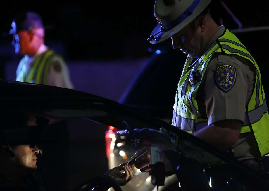 An officer  checks a person's driver's license at a California Highway Patrol driver's license and sobriety checkpoint in Livermore. Photo: Leah Millis, The Chronicle