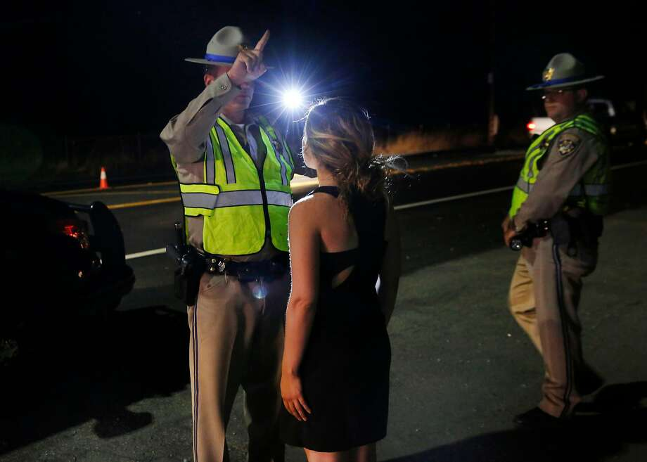 Officer B. Calero gives a specific sobriety test to a young woman suspected to be under the influence of marijuana at a California Highway Patrol driver license and sobriety checkpoint July 22, 2016 in Livermore, Calif. Photo: Leah Millis, The Chronicle