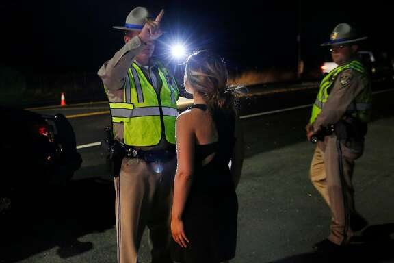 Officer B. Calero gives a specific sobriety test to a young woman suspected to be under the influence of marijuana at a California Highway Patrol driver license and sobriety checkpoint July 22, 2016 in Livermore, Calif.