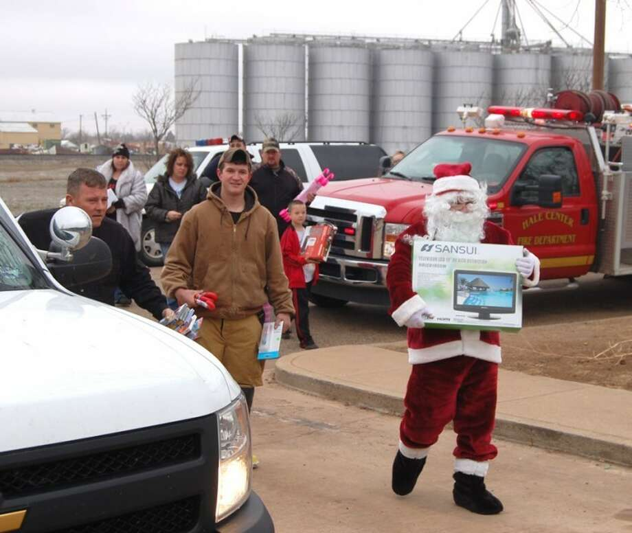 Doug McDonough/Plainview HeraldAccompanying Santa Claus on a delivery Thursday to a Santa Red and Blue recipient in Hale Center are Terry Timms (left), Melanie Cook, DeLisa Bailey, Jerrod Huffhines, Casey Parks, Bill Ayers and Kagen Ashley.