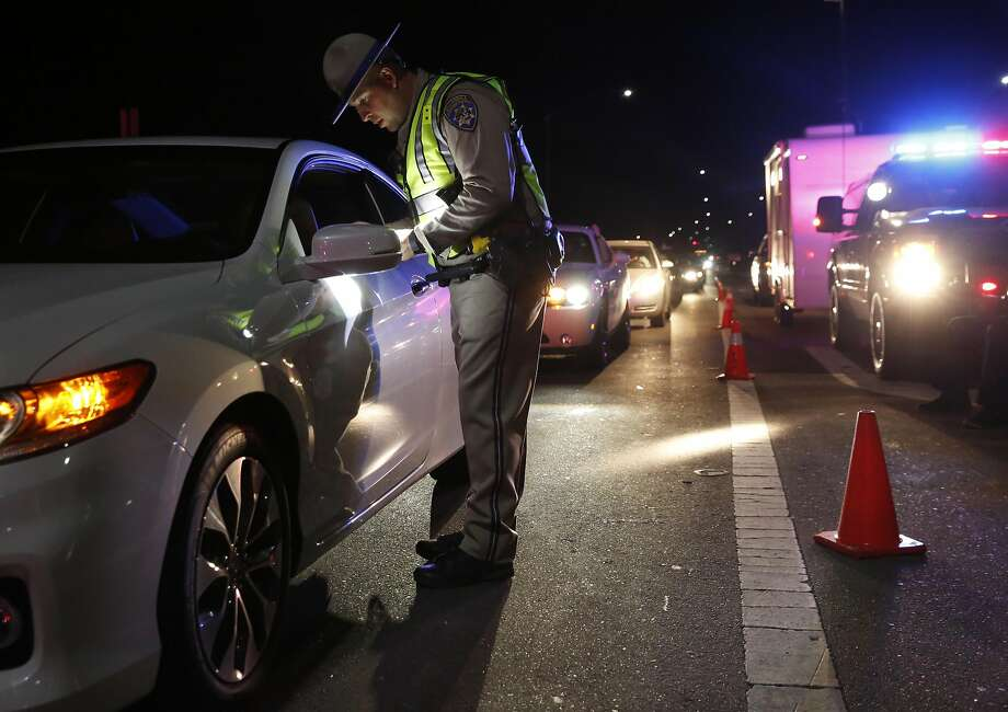 Officer Derek Reed checks a person's driver's license at a California Highway Patrol driver's license and sobriety checkpoint in Livermore. Photo: Leah Millis, The Chronicle
