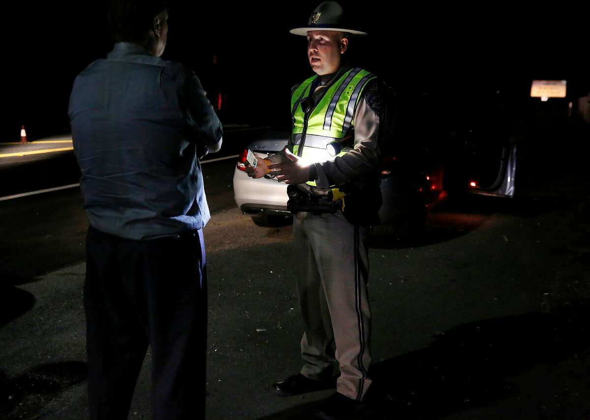 Officer Derek Reed gives a firm talking-to about the dangers of driving under the influence of marijuana to a man after giving him a sobriety test at a California Highway Patrol driver license and sobriety checkpoint July 22, 2016 in Livermore, Calif.