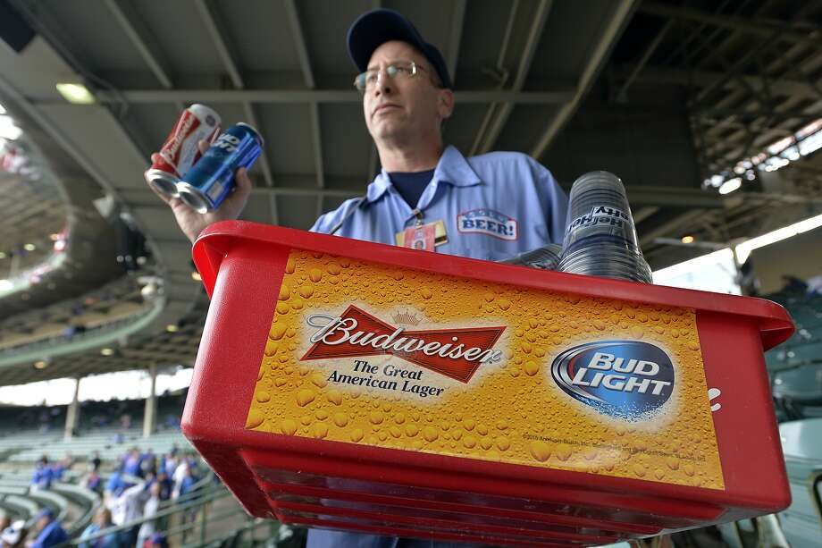 FILE - In this Tuesday, Oct. 13, 2015, file photo, a beer vender holds up Budweiser and Bud Light at Wrigley Field before Game 4 in baseball's National League Division Series between the Chicago Cubs and the St. Louis Cardinals in Chicago. Anheuser-Busch InBev, the world's largest beer maker, announced Wednesday, July 20, 2016, that it has reached an agreement with the Justice Department clearing the way for U.S. approval of its acquisition of SABMiller. (AP Photo/Paul Beaty, File) Photo: Paul Beaty, Associated Press