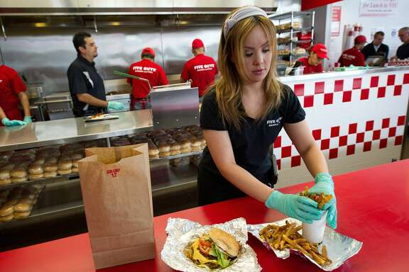 Cookie Bastos wraps up an order to go at the Five Guys restaurant in Dublin, California, on June 29, 2011.