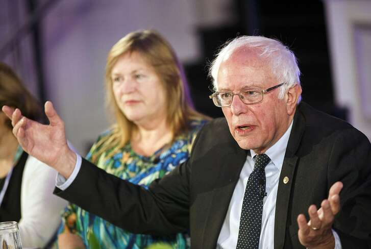 Senator Bernie Sanders, an independent from Vermont, speaks as his wife Jane Sanders listens during a Bloomberg Politics interview on the sidelines of the Democratic National Convention (DNC) in Philadelphia, Pennsylvania, U.S., on Tuesday, July 26, 2016. As the Democratic National Convention opened Monday in Philadelphia, a booing, jeering contingent of the Vermont senator's backers was so insistent about never supporting presumptive nominee Hillary Clinton that Sanders himself couldn't reel them in. Photographer: Patrick T. Fallon/Bloomberg