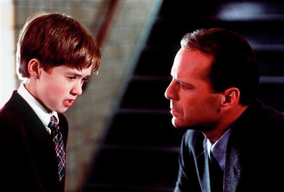 "FILE - In this publicity photo released by Spyglass Entertainment, Haley Joel Osment, left, and Bruce Willis appear in a scene from the film ""The Sixth Sense,"" a tale of a child who can see ghosts. Revealing secret endings and plot twists has brought on wrath since the dawn of cinema, straight through VCRS to streaming and DVRs. But exactly what is the magic formula for spoiler grace. (AP Photo/Spyglass Entertainment, Ron Phillips, File) Photo: RON PHILLIPS / SPYGLASS ENTERTAINMENT"