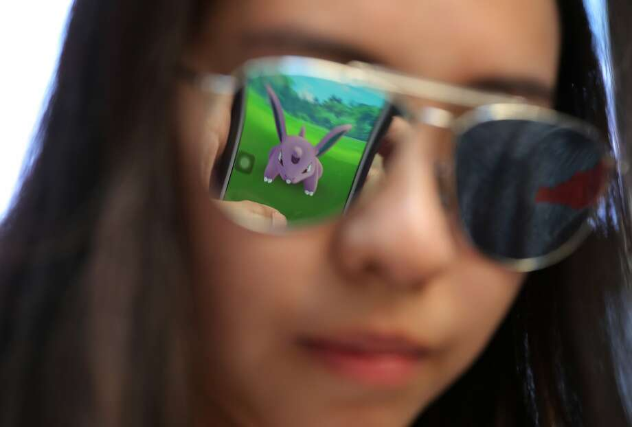 "A mobile screen is reflected on a fan's sunglasses as she plays ""Pokemon Go"" in Hong Kong, Monday, July 25, 2016. Pokemon fans participated in creatures hunting on Monday as the app was released to both iPhone and Android users. (AP Photo/Kin Cheung) Photo: Kin Cheung, Associated Press"