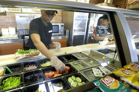 """FILE - In this March 3, 2015, file photo, workers make sandwiches at a Subway sandwich franchise in Seattle. Subway promises to ensure its """"Footlong"""" sandwiches measure up to settle a class-action lawsuit. The suit was sparked after a teenager posted a photo on Facebook showing his sandwich was only 11 inches. In October 2015, Subway's parent company, Doctors Associates, agreed to a preliminary settlement, which was granted final approval on Feb. 25, 2016. (AP Photo/Ted S. Warren, File)"""