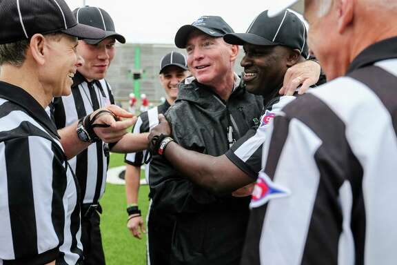 Marshall coach Doc Holliday greets the officials for the team's Green and White spring game on April 30, 2016, in Huntington, W.Va.