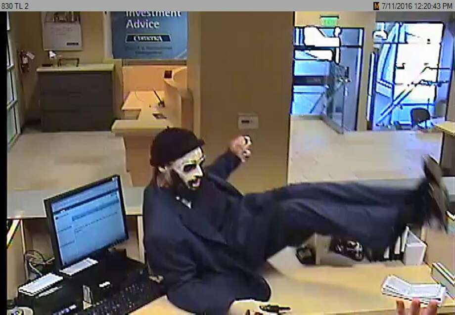 "The ""Dreaded Bandit"" is seen on a security camera jumping the counter of a Bay Area bank. Photo: FBI / FBI"