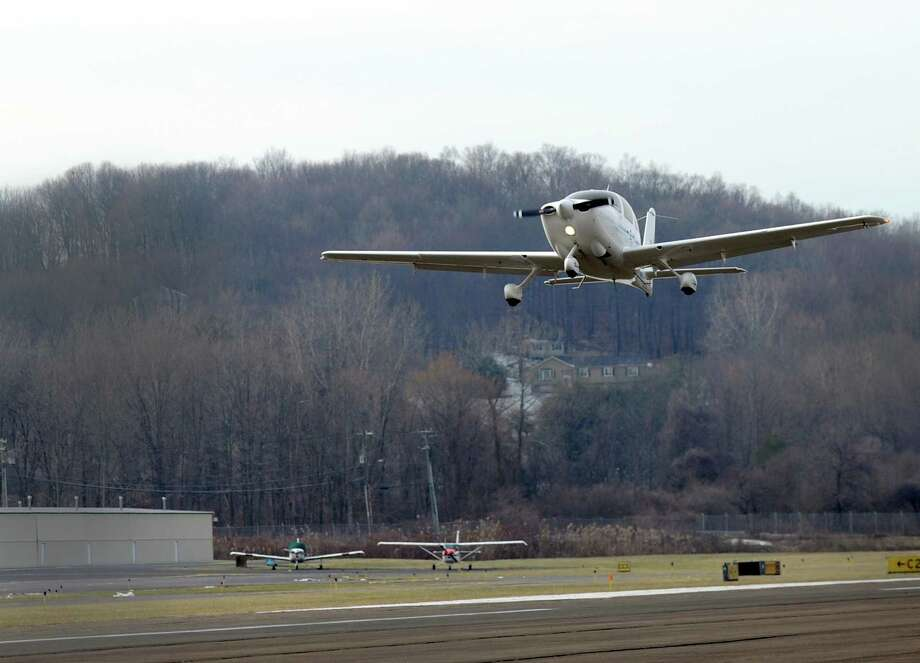 A plane takes off from Danbury Airport Friday, January 15, 2016. Backyard trees have grown so tall at the western approach of a Danbury Airport runway that the FAA has ordered the trees cut down at a cost of nearly $1 million, most of which will be paid for by the federal government. The money will be used to buy easements at a half dozen homes at the Ridgefield border where the trees will be removed. Photo: Carol Kaliff / Hearst Connecticut Media / The News-Times