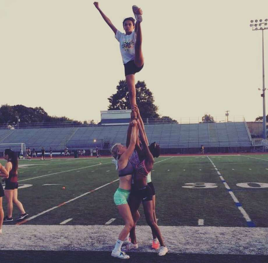 Members of the 2016-17 Norwalk High School cheerleading team practicing a couple of different stunts. Photo: Contributed: Kathy Foley