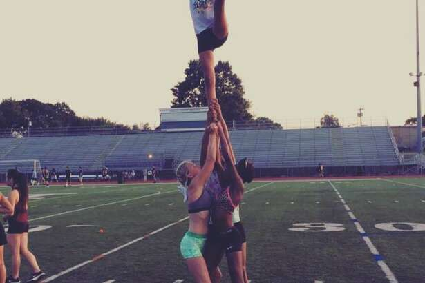 Members of the 2016-17 Norwalk High School cheerleading team practicing a couple of different stunts.