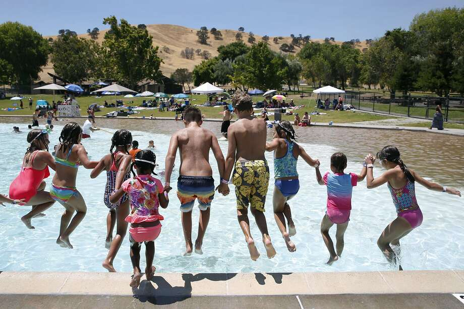 Kids seek relief from the heat with a group leap into the swimming pool at Contra Loma Regional Park in Antioch, Calif. on Tuesday, July 26, 2016. Triple digit temperatures are forecast in inland areas for the next few days. Photo: Paul Chinn, The Chronicle