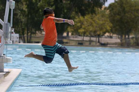 Julian Montanez leaps into the swimming pool at Contra Loma Regional Park in Antioch, Calif. on Tuesday, July 26, 2016. Triple digit temperatures are forecast in inland areas for the next few days.