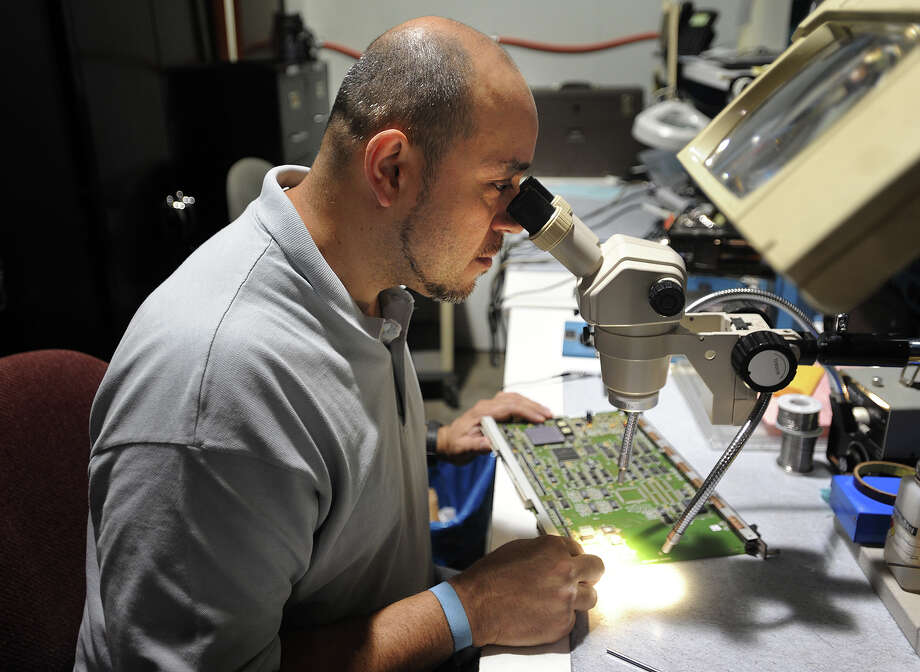 Network engineer Jose Lopez uses a microscope to diagnose repairs needed to a PWB, or circuit board, at General Datacomm's new offices in Oxford, Conn. on Tuesday, July 26, 2016. Photo: Brian A. Pounds / Hearst Connecticut Media / Connecticut Post
