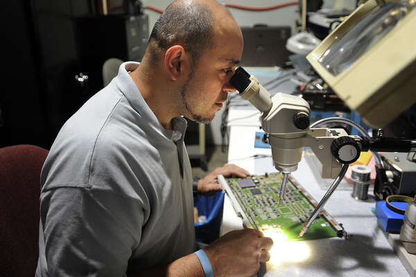 Network engineer Jose Lopez uses a microscope to diagnose repairs needed to a PWB, or circuit board, at General Datacomm's new offices in Oxford, Conn. on Tuesday, July 26, 2016.