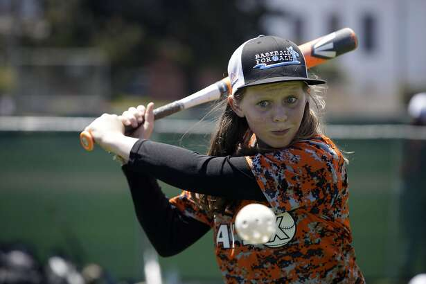 Cecelia McQuaid, 13, of the SF Bay Sox , focuses on the ball as she practices batting before the SF Bay Sox play the DC Force during the Baseball for All 2016 National Tournament at Moscone Recreation Center on Monday, July 25, 2016 in San Francisco, California.