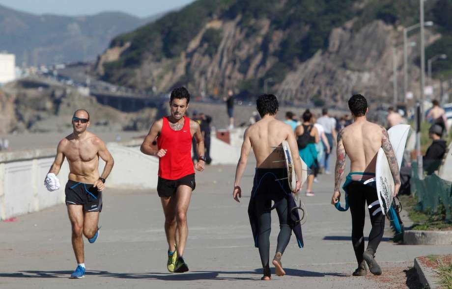 FILE-- Runners and surfers enjoy the warm weather at Ocean Beach in San Francisco on Feb. 2, 2015. More sunny skies and toasty temperatures are in store the rest of this week for the Bay Area. The Bay Area Quality Management District issued its 26th Spare the Air alert of the year on Saturday, Oct. 8, 2016. Photo: Jessica Christian / The Chronicle / /