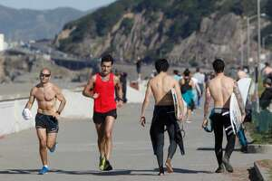 Runners and surfers enjoy the warm weather at Ocean Beach in San Francisco on Feb. 2, 2015. More sunny skies and toasty temperatures are in store the rest of this week for the Bay Area.