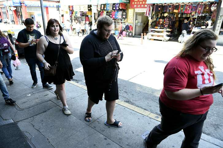 """Tyler Calcagno,Chastity Shilling, Dylan Davis, and Sarah Ayers and play Pokémon Go on Tuesday, July 26, 2016 in San Francisco, California. """"This is great area to play in theres lots of lures here,"""" said Davis."""