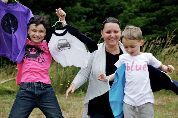 In this Thursday, July 7, 2016, photo, Martine Zoer poses for a photo with her sons Tyler, 8, left, and Tristan, 5, as they wear and display some of the gender-neutral clothing she creates, in Mill Creek, Wash. Zoer founded Quirkie Kids two years ago that marketed unisex pink shirts online, starting the business after her sons wanted to wear pink but she couldn't find anything in the boys' section. Her collection has since expanded to other colors, and she set up two Instagram accounts @stillagirl and @stillaboy that share such images of boys clutching flowers or girls playing with a toy car.