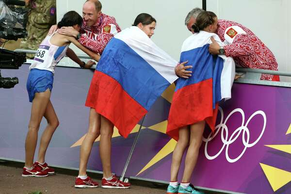 Russia coach Alexey Melnikov congratulates Olga Kaniskina, right, and Russia men's gold medalist Sergey Kirdyapkin congratulates Anisya Kirdyapkina, left, after the women's 20-kilometers race walk at the 2012 Summer Olympics in London. Russia gold-medalist Elena Lashmanova stands at center. The IOC's edict that each sport will determine if Russia's athletes will compete — because of a government coordinated doping scandal — is not onerous enough a sanction.