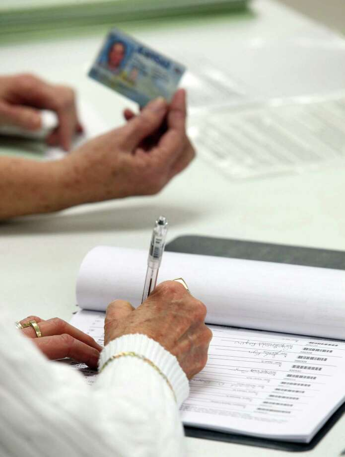 Election official checks the photo identification card of a voter  (AP file photo) Photo: Travis Morisse, MBO / AP2012
