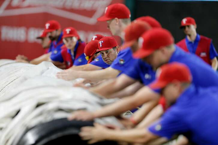 The Texas Rangers' grounds crew rolls up the tarp after a rain delay before the Rangers' baseball game against the Minnesota Twins on Saturday, July 9, 2016, in Arlington, Texas. (AP Photo/Brandon Wade)