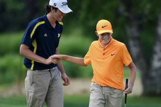 Ben James, right, 13, of Great River Golf Club in Milford, shakes hands with his caddy, Dylan Destafano, 18, after making a putt during day two of the Connecticut State Golf Association's 82nd Connecticut Open Championship at Woodway Country Club in Darien, Conn. Tuesday, July 26, 2016.
