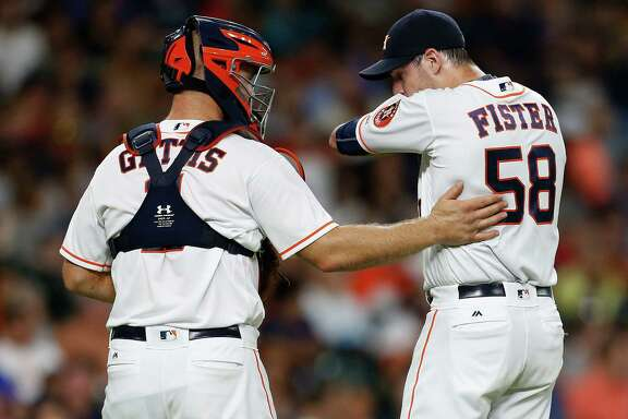 Houston Astros starting pitcher Doug Fister (58) chats with catcher Evan Gattis (11) during the third inning of an MLB game at Minute Maid Park, Tuesday, July 26, 2016, in Houston.